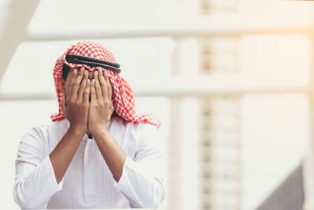 Arab young man sitting with his hands close to his face and felt sorry for despair in life.