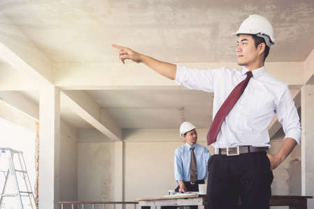 Architects who are standing are pointing their hands at building confidence. There is a background worker blurry.