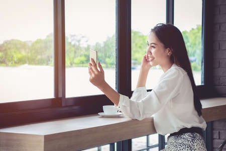 An Asian girl is taking her own picture during a coffee break during the day.