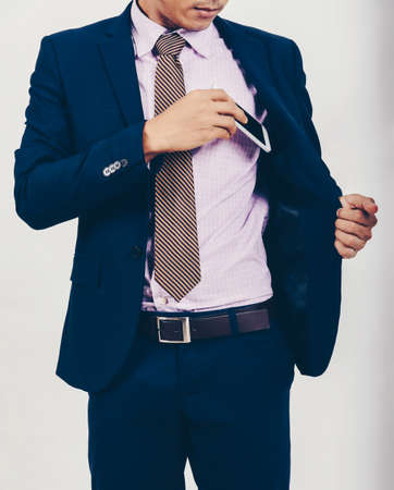 An Asian businessman is taking a smartphone from his pocket. Archivio Fotografico