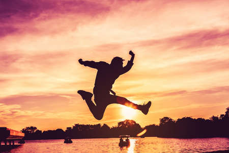 One man is jumping in the air, he is very happy in life with sunset as background.Silhouette image Reklamní fotografie