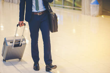 Businessmen leave with baggage at the airport.