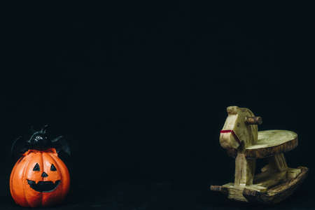 Doll head orange pumpkin's and Wooden horse toys are happy holidays Halloween.