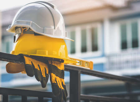 Un casque blanc et jaune avec des gants est placé sur une clôture de maison en acier.