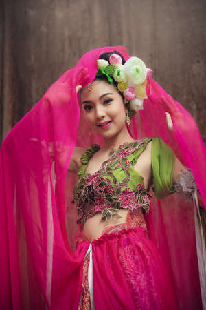 Asian fairy goddess adorned with lotus flowers, she was smiling beautifully on  wooden background.
