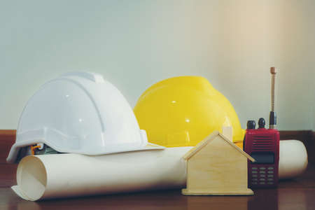 White and yellow helmet with wooden houses and various devices that are placed on a wooden floor.