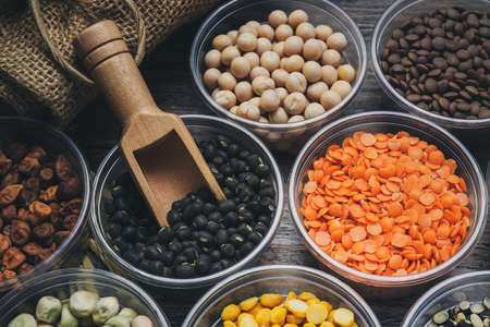 Different types of cereal beans that have a variety of nutritional benefits on the wooden floor.