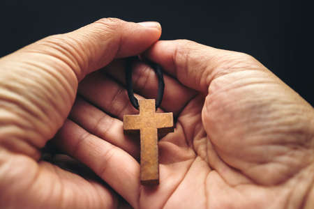 The crucifix is in the hands of a man who is praying for the blessing of his god with faith. Imagens