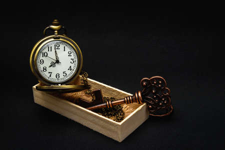 The old clock and key that were in a wooden box placed on a black background. 스톡 콘텐츠