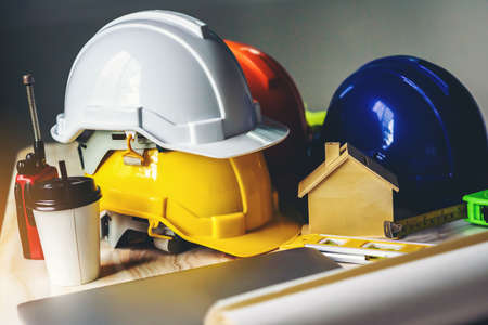 White, yellow and blue safety helmets for workers' safety projects in the position of engineers and all necessary equipment placed on the table. Foto de archivo - 135065043