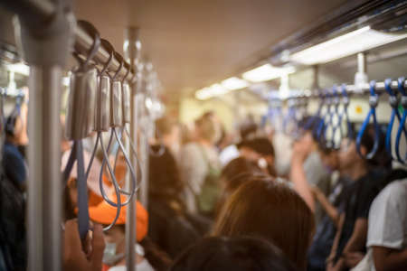 Many people are traveling by electric train during rush hour.This image is soft Focus.
