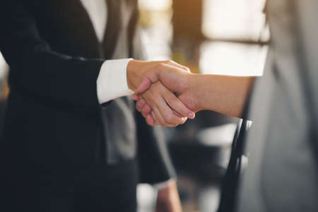 The hand of a businesswoman is shaking hands, check hands reached a business agreement. Stockfoto