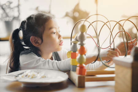 An Asian girl is playing toys while eating.