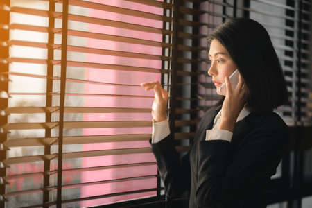An Asian working woman was standing on the phone near the window.
