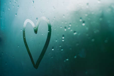 Heart shape caused by steam that is on the glass.