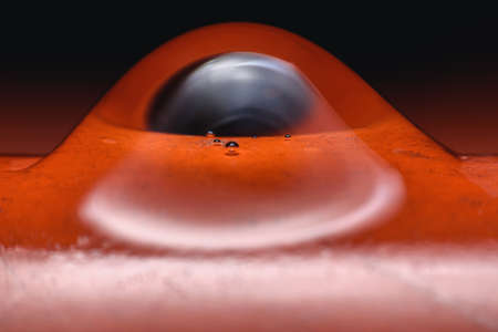 One drop of water is dropping over a red object with a black background.This image is soft focus.