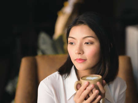 A black haired asian woman is resting and refreshing coffee in the morning.