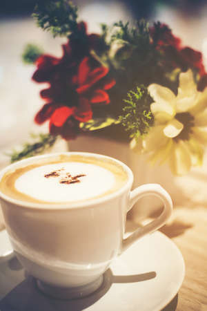 Cappuccino coffee placed on a wooden table and blurred floral background.