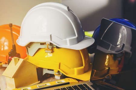 White, yellow and blue safety helmets for workers' safety projects in the position of engineers and all necessary equipment placed on the table.