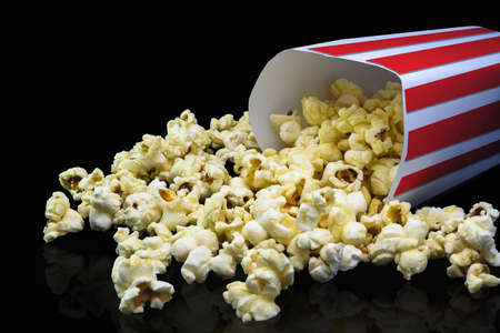 Delicious popcorn that is ready to eat that is on a black background.