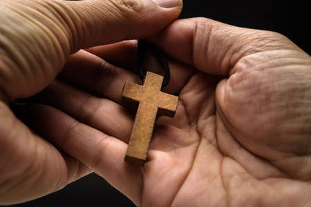 The crucifix is in the hands of a man who is praying for the blessing of his god with faith.