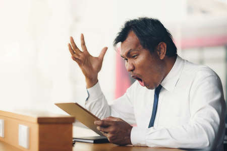 A middle-aged businessman holding a tablet is shocked by what happened to the screen.