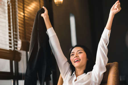 An Asian business woman is raising hands and smiling, happy with the work done.