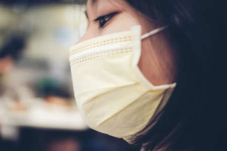 An Asian female teenager wears a surgical mask to protect against a new strain of viruses.
