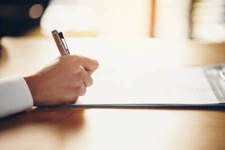 Hand of a businessman holding a pen is analyzing, business planner.For profit and stability of business sustainability.