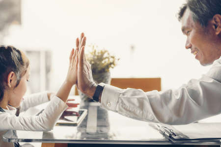 Asian father and daughter are high five happily touch each other's hands. Focus on the hands.