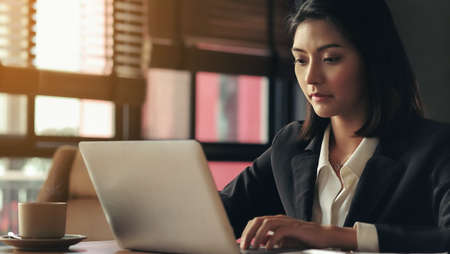 An Asian businesswoman is working her laptop intently.