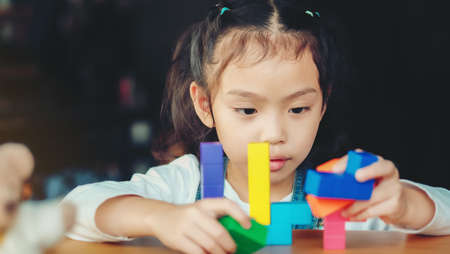Little Asian girls are playing toys to enhance skills and learning.