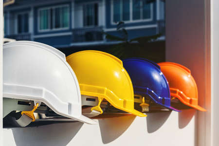 White, yellow and other colored safety helmets for workers' safety projects in the position of engineers or workers on concrete walls in the city. Stockfoto