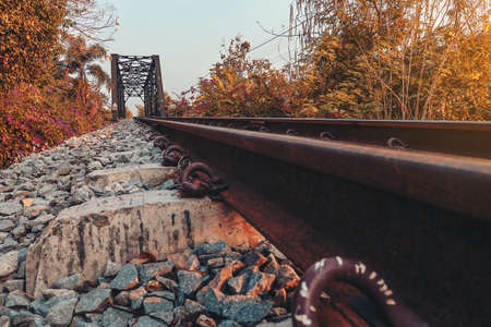 Railroad tracks with rocky tracks, looking far away to the evening sun.
