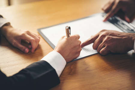 The hand of a business man is using the index finger to let the customer sign the contract, contract, business agreement.