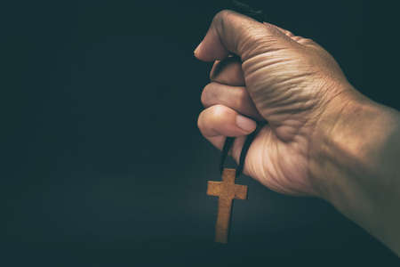 The crucifix is in the hands of a man who is praying for the blessing of his god with faith. Stockfoto