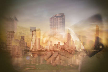 The hand of a business person is hands shaking against the big city in the background.Double Exposure Image. Stockfoto