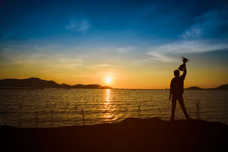 The shadow of the silhouetted man is happy and holds the trophy in the morning sun.