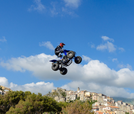 Scalea, ITALY - May 13, 2018. The freestyle Quad bike pilot makes a jump with a high jump with a trick.