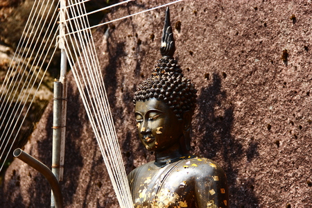 venerable: Buddha statue with rock background Stock Photo