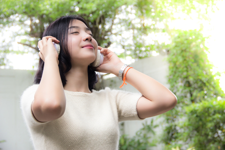 Pretty asian girl listening music with her headphones in the green garden and fair light