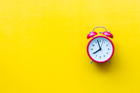 A red alarm clock with eight oclock on yellow  background with copyspace