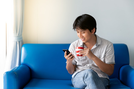 Handsome Asian man using mobile phone while drinking some coffee and sitting on blue sofa at morning