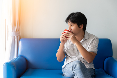 A man drinks coffee in the morning while sitting on the blue sofa. He looks at outside and thinks to find creative ideas and inspiration