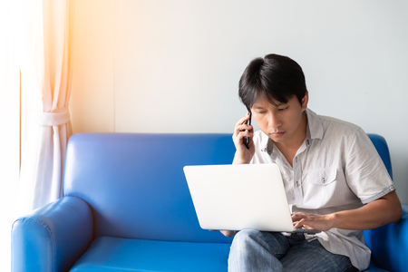 A man using laptop for works and online activities while talking on mobile phone and sitting on blue sofa at the morning time 写真素材