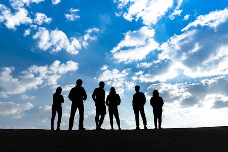 Silhouette group of people standing with blue sky background, teamwork and inspiration concept 写真素材