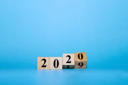 Happy New year concept. Wooden block cube of 2020 year number on blue isolate background, mininalist style