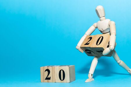 Happy New year 2020 celebration concept with Wooden human doll is carrying wood cube of twenty number on blue isolate background