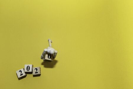 Happy New year 2020 celebration concept with top view Wooden human doll is carrying wood cube of zero number on yellow isolate background