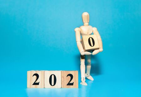 Happy New year 2020 celebration concept with Wooden human doll is carrying wood cube of zero number on blue isolate background